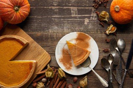 Foto de Vista superior de la deliciosa tarta de calabaza cerca de calabazas enteras, cubiertos, canela, avellanas y physalis en la superficie de madera oscura - Imagen libre de derechos