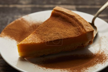 Photo for Close up view of delicious pumpkin pie with cinnamon powder on white plate on dark wooden table - Royalty Free Image