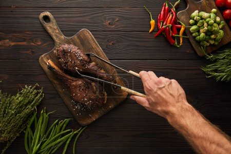 Photo for Cropped view of man taking tasty meat from cutting board with tweezers - Royalty Free Image