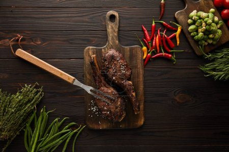 Photo for Top view of meat, chili peppers, cherry tomatoes, green peas, greenery, brussels sprouts and meat fork - Royalty Free Image