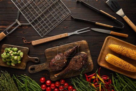 Photo for Top view of meat, corn, chili peppers, cherry tomatoes, green peas, greenery, brussels sprouts on cutting board and grill tools - Royalty Free Image