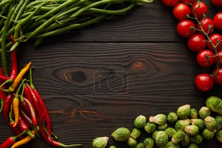 Photo for Top view of chili peppers, cherry tomatoes, green peas, brussels sprouts on wooden table - Royalty Free Image