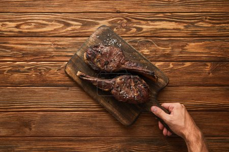 Photo for Cropped view of man holding cutting board with tasty meat - Royalty Free Image