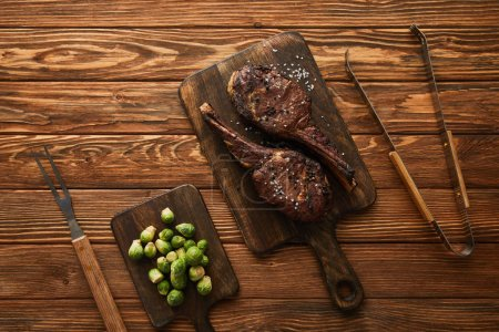 Photo for Top view of meat and brussels sprouts on cutting boards with grill tools - Royalty Free Image