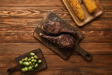 Photo for Top view of meat, corn and brussels sprouts on cutting boards - Royalty Free Image