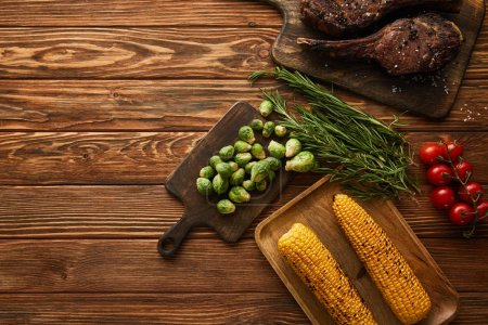 Photo for Top view of meat, corn, cherry tomatoes, greenery, brussels sprouts on cutting board - Royalty Free Image