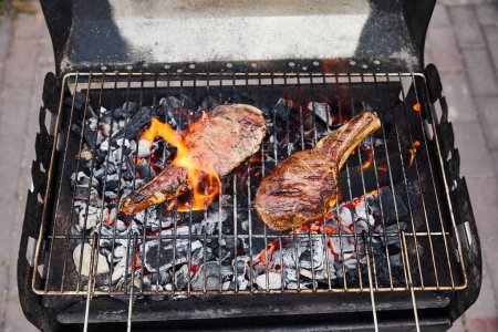 Photo for Top view of meat grilling on barbecue grid and coal pieces outside - Royalty Free Image