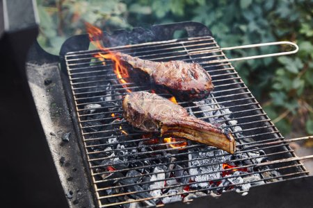 Photo for Tasty meat grilling on barbecue grid and coal pieces outside - Royalty Free Image