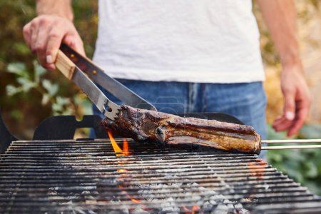 Photo for Cropped view of man with tweezers grilling meat on barbecue grid - Royalty Free Image