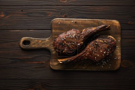 Photo for Top view of tasty meat with spices on cutting board - Royalty Free Image