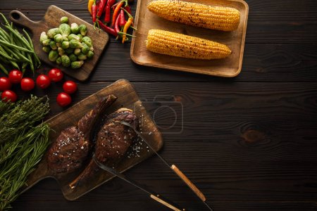 Photo for Top view of meat, corn, chili peppers, cherry tomatoes, green peas, greenery, brussels sprouts on cutting board, tweezers - Royalty Free Image