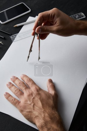 Photo for Cropped view of architect drawing with compass on white paper - Royalty Free Image