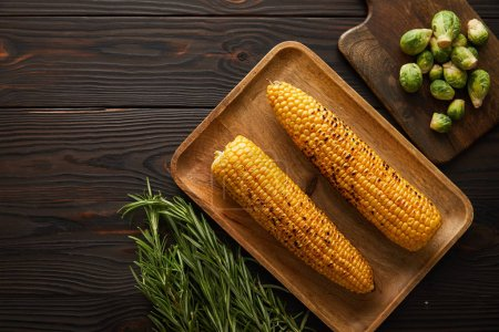 Photo for Top view of corn, greenery, brussels sprouts on cutting board - Royalty Free Image