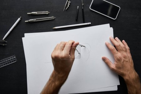 Photo for Cropped view of man drawing circle on paper with compass - Royalty Free Image