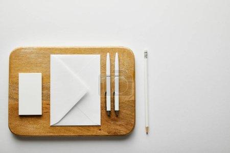Draufsicht auf Umschlag, Visitenkarte und Stifte auf Holzplatte, Bleistift