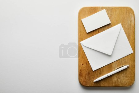 Photo for Top view of envelope, empty business card and pen on wooden board - Royalty Free Image