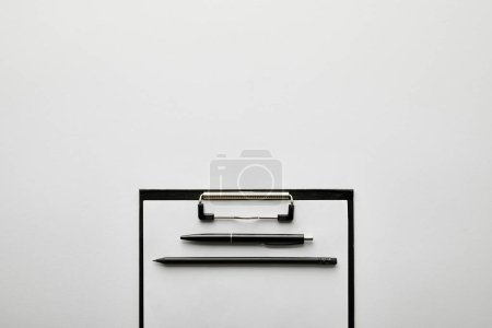 Photo for Top view of empty clipboard, pen and pencil on table - Royalty Free Image