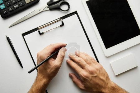 Photo for Cropped view of man writing in clipboard with pen - Royalty Free Image