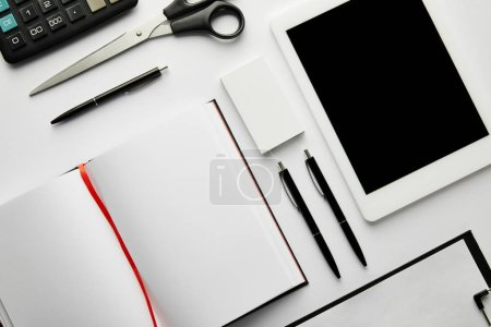 Photo for Top view of clipboard, notebook, pens, business card, scissors, calculator and digital tablet - Royalty Free Image