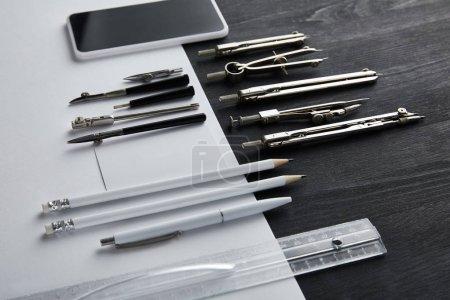 Photo pour Papier blanc avec espace de copie et boussoles, règle, crayons, smartphone, stylo sur table noire et bois - image libre de droit