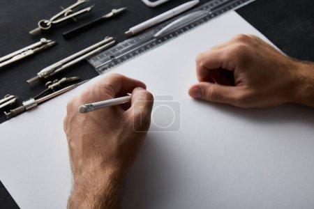 Photo pour Vue recadrée de l'homme d'affaires écrivant sur papier avec crayon - image libre de droit