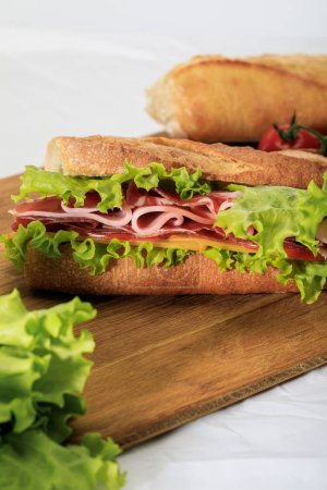 Photo for Selective focus of fresh sandwich with lettuce, ham, cheese, bacon and tomato on wooden cutting board - Royalty Free Image