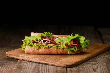 Photo for Fresh sandwich with lettuce, ham, cheese, bacon and tomato on wooden cutting board isolated on black - Royalty Free Image