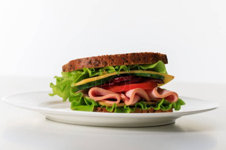 Photo for Fresh sandwich with lettuce, ham, cheese, bacon and tomato on plate isolated on white - Royalty Free Image
