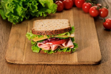 Photo pour Selective focus of fresh sandwich on wooden cutting board near lettuce and cherry tomatoes - image libre de droit