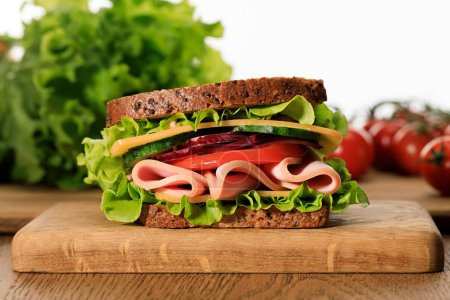 Photo for Fresh sandwich with lettuce, ham, cheese, bacon and tomato on wooden cutting board isolated on white - Royalty Free Image
