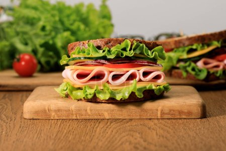Photo for Fresh sandwich with lettuce, ham, cheese, bacon and tomato on wooden cutting board isolated on grey - Royalty Free Image