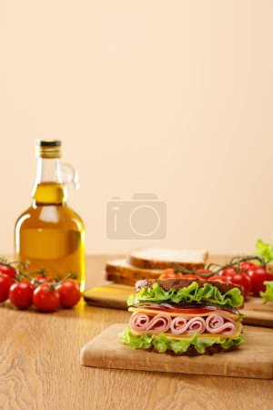 Photo pour Selective focus of fresh sandwich near lettuce, bread, cherry tomatoes and oil on wooden table isolated on beige - image libre de droit