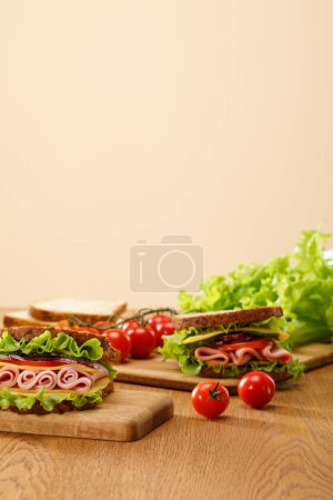Photo for Selective focus of fresh sandwich near lettuce, bread, cherry tomatoes on wooden table isolated on beige - Royalty Free Image