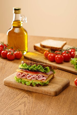Photo for Selective focus of fresh sandwich near lettuce, bread, cherry tomatoes and oil on wooden table isolated on beige - Royalty Free Image
