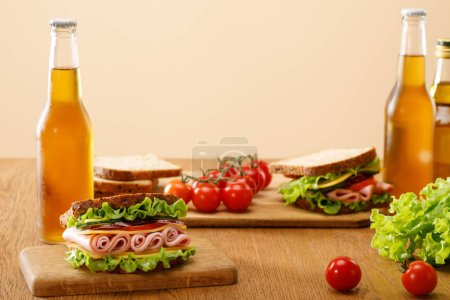 Photo for Selective focus of fresh sandwich with lettuce, ham, cheese, bacon and tomato near bottles of beer at wooden table isolated on beige - Royalty Free Image