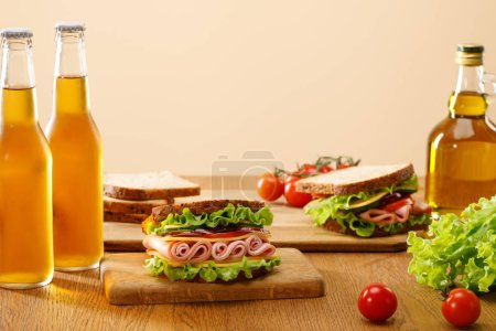 Photo for Selective focus of fresh sandwiches with lettuce, ham, cheese, bacon and tomato near bottles of beer at wooden table isolated on beige - Royalty Free Image
