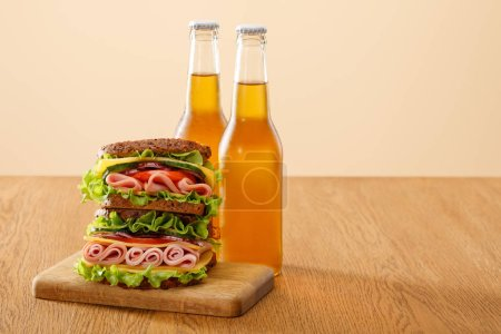 Photo for Fresh sandwich with lettuce, ham, cheese, bacon and tomato near bottles of beer at wooden table isolated on beige - Royalty Free Image