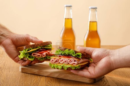 Photo for Cropped view of men holding fresh sandwiches with lettuce, ham, cheese, bacon and tomato near bottles of beer at wooden table isolated on beige - Royalty Free Image