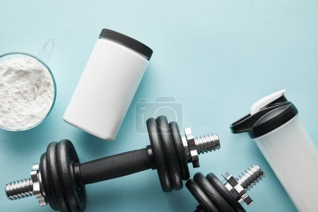 top view of dumbbells near sports bottle and protein powder on blue