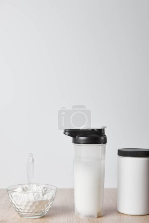 Photo for Protein shake in sports bottle near jar and glass bowl with protein shake isolated on grey - Royalty Free Image