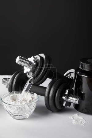 Photo for Glass bowl with protein powder near dumbbells on black - Royalty Free Image