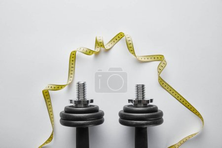 Photo for Top view of heavy black dumbbells near yellow measuring tape on white - Royalty Free Image