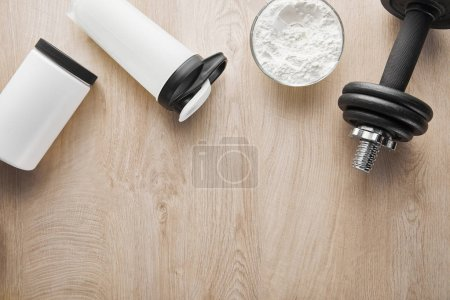 top view of dumbbell near sports bottle and jar on wooden surface