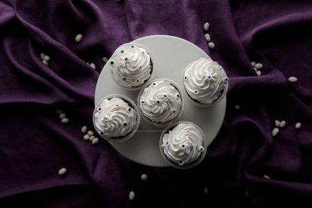 Draufsicht auf köstliche Halloween-Cupcakes mit weißer Sahne auf lila Tuch