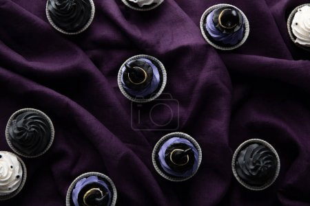 Photo for Top view of delicious Halloween cupcakes on purple cloth - Royalty Free Image