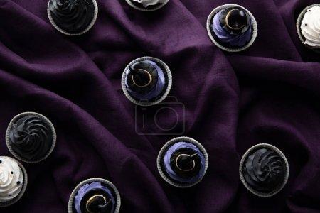 Foto de Vistas superiores de deliciosos cupcakes de Halloween en tela púrpura. - Imagen libre de derechos
