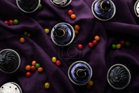 Foto de Vistas superiores de deliciosos cupcakes de Halloween con cucharas en tela púrpura. - Imagen libre de derechos