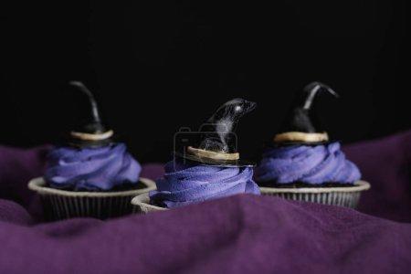 Photo pour Savoureux cupcakes Halloween avec crème bleue et chapeaux de sorcière décoratifs sur tissu violet isolé sur noir - image libre de droit