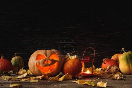Photo pour Citrouille d'Halloween fantasmagorique sculptée, feuilles automnales et bougie allumée sur table rustique en bois sur fond noir - image libre de droit