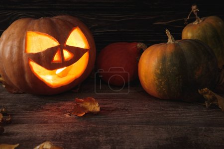 Photo for Carved spooky Halloween pumpkin, autumnal leaves and burning candle on wooden rustic table - Royalty Free Image